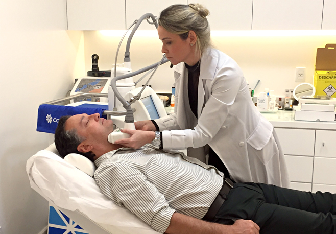 Homens buscam tratamento para a região do pescoço. Na imagem, Dra. Marcella Alves, dermatologista, administra procedimento de criolipólise no paciente Angelo Zamorano.